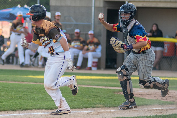 La Crosse's catcher Nicholas Kahle (right) chases Jake Ortega of the MoonDogs in a run down during Friday's Northwoods League game. Photo by Jackson Forderer