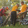 Staff at the Hill Climb help Wally Krech with a broke down motocross bike. Krech, from St. Paul, raced in the Super Senior division at the Hill Climb hosted by Kato Cycle Club. Photo by Jackson Forderer