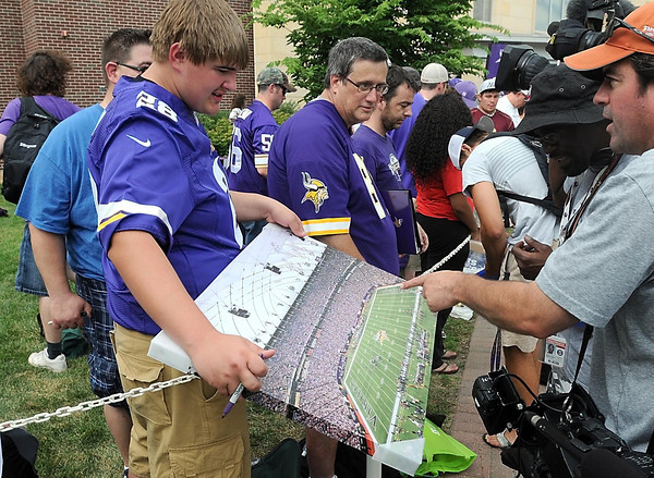 Treyton Brochardt of Litchfield shows off a canvas print of Mall of America field as Minnesota Vikings players arrive for the team's training camp Thursday at MSU. This is the last season the team will play at the Metrodome.