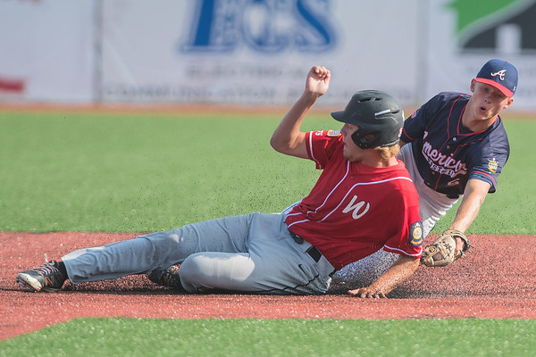 Mankato American's Ryan Kuechle (right) tries to get a tag on Worthington's Eric Heidebrink as Heidebrink attempted to steal second base. Heidebrink was called safe on the play, but the American team edged Worthington 6-5 to avoid elimination from the Sub-state tournament. Photo by Jackson Forderer