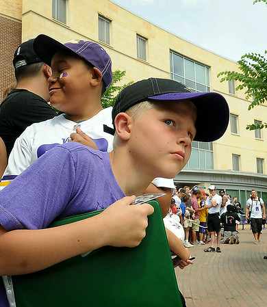 Young Vikings fans T.J. Cusciotta of Hanover, Minn. (front) and Clayton Nichols of Burlington, Iowa had prime spots at the beginning of autograph row to intercept players as they arrived for preseason training camp on Thursday at Minnesota State University, Mankato. Photo by John Cross
