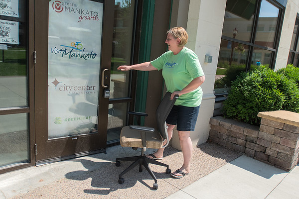 Joy Leafblad, the new Mankato Sports Commission Director, opens the door to the new offices for Greater Mankato Growth, Visit Mankato, City Center Partnership and GreenSeam in the Graif Building while moving office furniture to the new location. Photo by Jackson Forderer