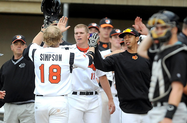 Mankato MoonDogs teammates congratulate Chase Simpson after his two-run home run in the first inning against Rochester Wednesday at Franklin Rogers Park.