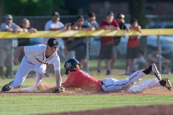 Mankato East's Ryan Kuechle makes a force out at third base before a sliding Mankato West Andrew Mihm could reach the base during Thursday's Section 2AAA playoff game played at Wolverton Field. Photo by Jackson Forderer