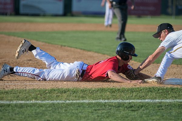 Mankato West's Nathan Phinney slides into third base safely ahead of a tag from Mankato East's Ryan Kuechle during Thursday's game. Photo by Jackson Forderer