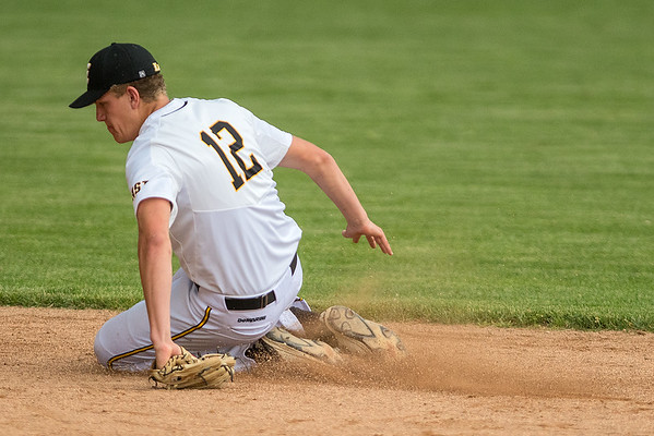 Mankato East's Nolan Michels slides on the ground after fielding a ground ball hit by a Marshall batter in the first inning of the Section 2AAA playoff game started in New Ulm. The game was postponed due to rain. Photo by Jackson Forderer