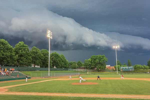 Jack Clifford delivers a pitch to a Marshall batter as storm clouds rolled into Johnson Park in New Ulm during Tuesday's Section 2AAA playoff game. The game was postponed until Thursday due to the inclement weather. Photo by Jackson Forderer
