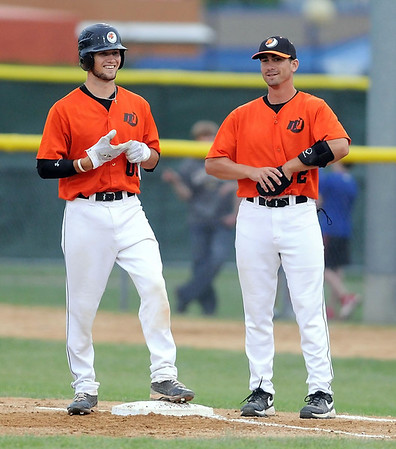 Mankato MoonDogs first base coach Cody Fick talks with baserunner Chase Fowler during a recent game.