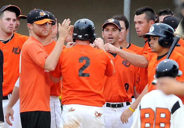 Mankato MoonDogs' Cody Ferrell (2) is congratulated by manager Mike Orchard (center) and the rest of the team after scoring during the MoonDogs' 6-run first inning Friday at Franklin Rogers Park.