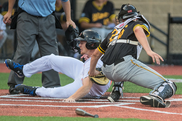 CJ Huntley of the Mankato MoonDogs slides safely into home plate just barely ahead of a tag applied by Willmar Stingers' catcher Matt Malkin. Photo by Jackson Forderer