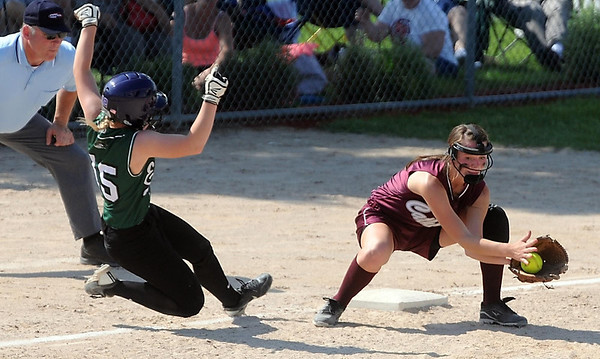 New Life Academy's Kayla Binsfeld lunges back to third base as New Ulm Cathedral's MacKinnon Elenz fields the throw during the Class A championship game Friday at Caswell Park. Photo by Pat Christman