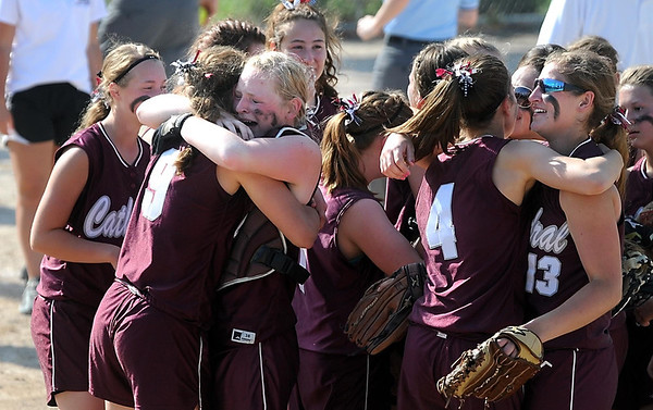New Ulm Cathedral pitcher Anna Mohr (9) and catcher Karlee Pfaff embrace as the team celebrates its Class A state softball championship win over New Life Academy Friday at Caswell Park. Photo by Pat Christman
