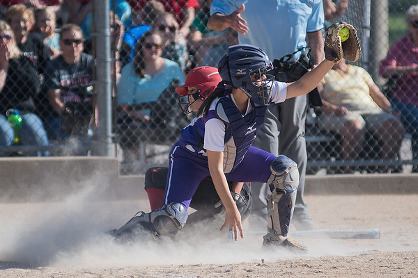 New Ulm catcher Camryn Schiro holds the ball up to show the umpire she made the force at home on Mankato West's Emily Veroeven in the Section 2AAA championship game played at Caswell Park. The Scarlets won the game 8-2 to advance to the state tournament. Photo by Jackson Forderer