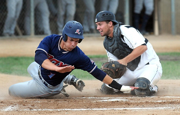 Pat Christman<br /> St. Cloud's Daniel Comstock is tagged out by MoonDogs' catcher Matt Wollenzin before he can touch home plate during the second inning Friday at Franklin Rogers Park.