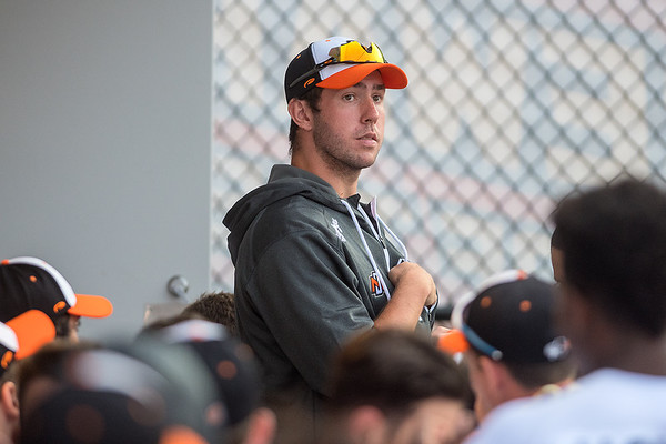 Adam Lukas stands in the dugout with the Mankato MoonDogs team during an off night from pitching. Lukas is a sophomore pitcher from Evansville. Photo by Jackson Forderer