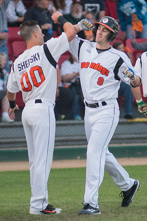 Jake Shepski (00) and Ryan Kreidler (9) of the MoonDogs bash forearms after Kreidler's home run against the Bismarck Lark in Friday's game. Shepski and Kreidler hit back-to-back home runs in the MoonDogs win. Photo by Jackson Forderer