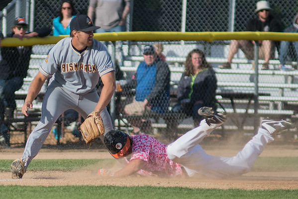 Kyle Cuellar of the MoonDogs slides head first into third base as the Bismarck Larks' Newt Johnson waits for the throw. The MoonDogs lost to the Larks 9-7 on Saturday. Photo by Jackson Forderer