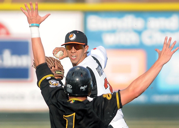Pat Christman<br /> Mankato MoonDogs shortstop Ryan Rosthenhausler turns a double play despite the outstretched arms of Willmar's Brian Olson Tuesday at Franklin Rogers Park.