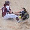 New Ulm Cathedral's Jenna Helget (left) slides into third base safely after Badger/Green Bush-Middle River's Kinsley Hanson dropped the ball while trying to apply a tag during Thursday's state quarterfinal game played at Caswell Park. Cathedral won their first game 10-2 against Badger to move on to the semifinals. Photo by Jackson Forderer