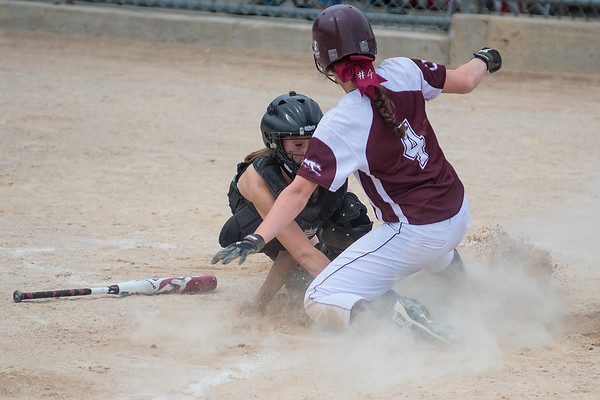 New Ulm Cathedral's Jenna Helget slides around a tag by Badger/Greenbush-Middle River catcher Jacey Wojchowski. Photo by Jackson Forderer