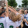 Maple Lake softball players rush their team captains after they received the first place trophy for the Class AA state softball tournament. Photo by Jackson Forderer