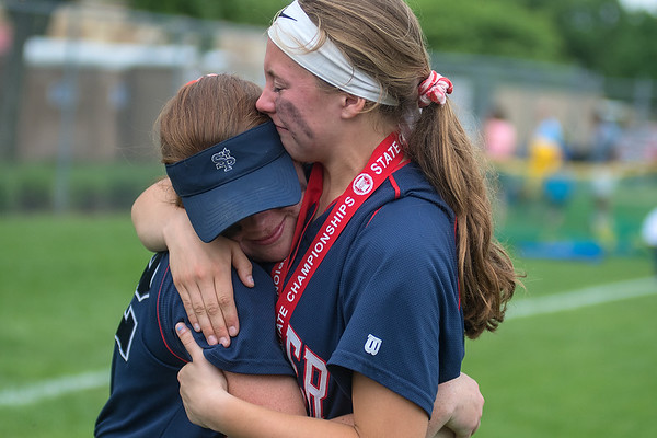 Olivia McCabe (left) and Kayla Oeltjenbruns of St. Peter share a moment after the team took second place in the Class AA state softball tournament on Friday at Caswell Park in North Mankato. Photo by Jackson Forderer