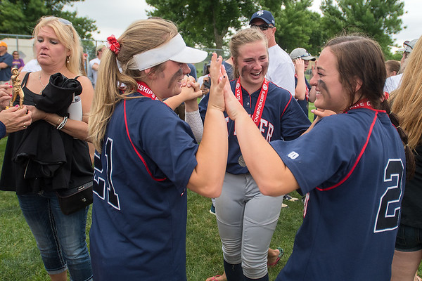 McKenna Reese (left), Allie McCabe (right) and Olivia Stevens (center) congratulate each other after taking second place in the state softball tournament. Photo by Jackson Forderer