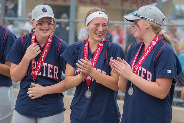 From left, St. Peter players Eleanor Rosberg, Kayla Oeltjenbruns and Breanna Hagen laugh after receiving their second place medals at the state softball tournament. From left, Photo by Jackson Forderer