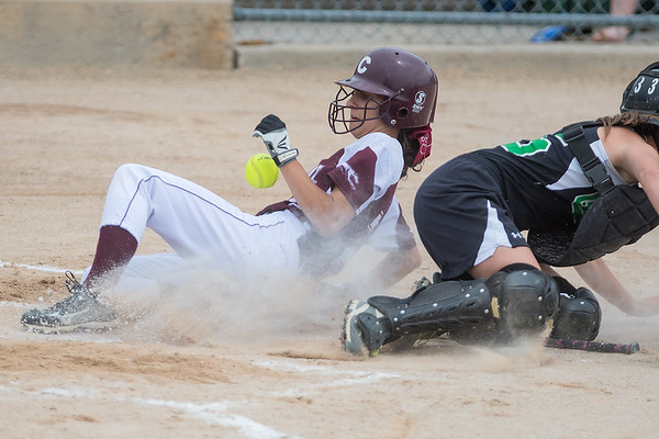 New Ulm Cathedral's Sarah Mohr slides safely into home after Badger/Greenbush-Middle River's Jacey Wojchowski mishandled the throw home. Photo by Jackson Forderer