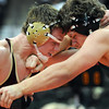 Blue Earth Area's Kysten Zierke locks up with Holdingford's Mitch Mesmaan during their State Class A 195 pound quarterfinal match Friday.