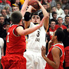 Mankato East's Brandon Adema shoots over Mankato West's Jake Dale during the first half Wednesday at the West gym.