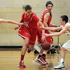 Mankato West's Austin Majeske (center) tries to slip between Mankato East's Matt Bornholdt (left) and Nic Seiler during the first half Wednesday at the West gym.