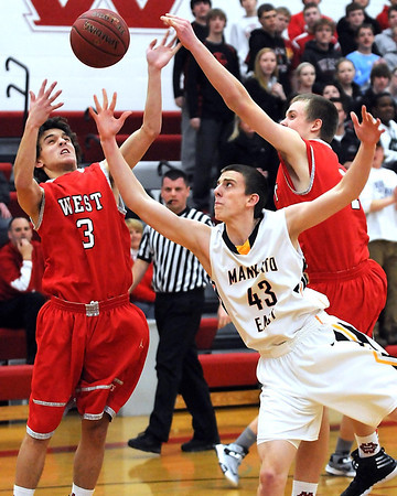 Mankato West's Tyler Stoffel (3) and Jake Dale (1) and Mankato East's Matt Bornholdt (43) reach for a rebound during the first half Wednesday at the West gym.