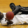 Rochester Century's Jamal Brown (in white) and Mankato East's Mattu Chuol scramble for a loose ball during the first half Thursday at the East gym.