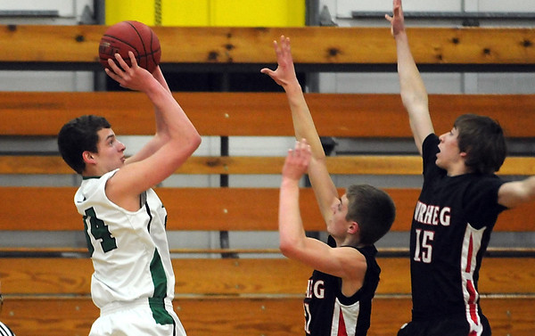 Pat Christman<br /> Waterville-Elysian-Morristown's Zac Olson takes a shot over the outstretche arms of New Richland-Hartland-Ellendale-Geneva's Oakley Baker (21) and Macoy Schwierjohan (21) during the first half Friday at the Mankato East gym.