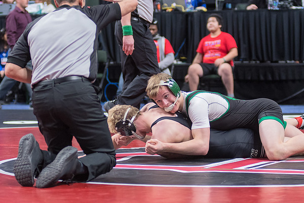 Wyatt Simon of Maple River looks to the referee for a 2-point take down signal in the final moments of the third period in the Class A 160-lb. division. Simon won his match to take 5th place overall in the weight class. Photo by Jackson Forderer