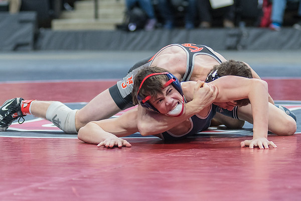 Blake Legred of United South Central bites his chinstrap while trying to break free from the hold of Mark Buringa of St. Charles in the Class A 138-lb. championship match. Legred lost a close match to take second place in the state tournament. Photo by Jackson Forderer