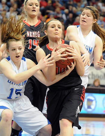 New Richland-Hartland-Ellendale-Geneva's Hannah Lundberg struggles for a rebound with Braham's Jenna Winter (15) and Dani Braund during the first half of their State Class AA championship game Saturday at Target Center.