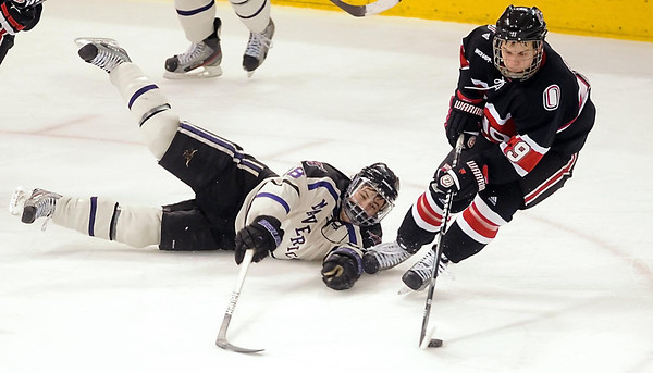 University of Nebraska-Omaha's James Polk steals the puck from Minnesota State's Matt Leitner (18) as he falls during the second period of their WCHA tournament game Saturday at the Verizon Wireless Center.