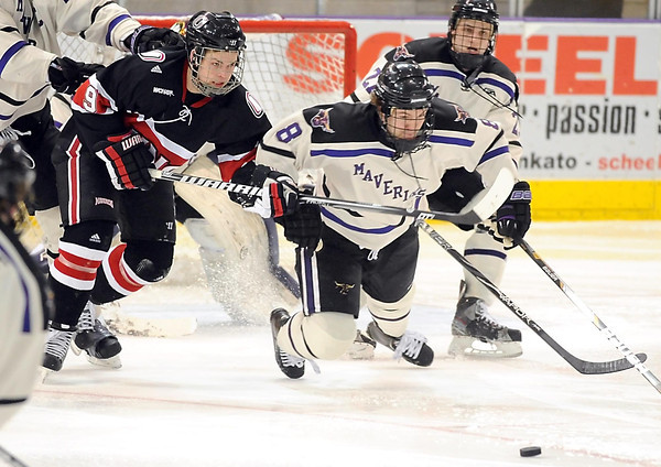University of Nebraska-Omaha's James Polk (9) and Minnesota State's Max Gaede race for the puck during the third period of their WCHA tournament game Saturday at the Verizon Wireless Center.