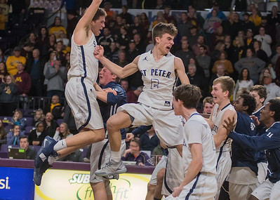 Ethan Volk (center) and Wyatt Olson (left) of St. Peter jump in celebration as their teammates join them after the Saints defeated Jordan 71-68 to gain a berth in the Class AA boys state basketball tournament. Photo by Jackson Forderer