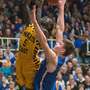 Andrew Morgan of Waseca blocks a shot put up by Joich Gong of Mankato East in the Section 2AAA championship game held at Gustavus on Thursday. Morgan finished the game with 22 points and 11 rebounds for the Bluejays in their 63-54 victory. Photo by Jackson Forderer