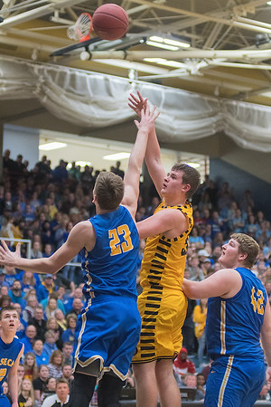 Mankato East's Jordan Merest gets a hook shot off over Waseca's Andrew Morgan in the second half as the Cougars tried to mount a comeback against the Bluejays. Photo by Jackson Forderer