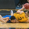 Malik Willingham (left) of Waseca has his arm trapped underneath Mankato East's Jax Madson as both hustled for a loose ball in the second half of Thursday's game. Photo by Jackson Forderer