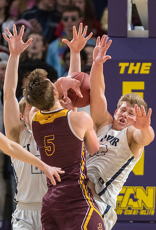 Seth Lokensgard (right) of St. Peter takes a charge from Jordan's Ryan Fridges in the first half of Friday's Section 2AA championship game. St. Peter came back from being down 10 points at the half and won 71-68. Photo by Jackson Forderer