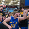 Waseca boys basketball players Matt Olsem (42) and Malik Willingham (right) hoist up the Section 2AAA championship trophy as their teammates rushed to join in the celebration after the Bluejays beat Mankato East 63-54. Photo by Jackson Forderer