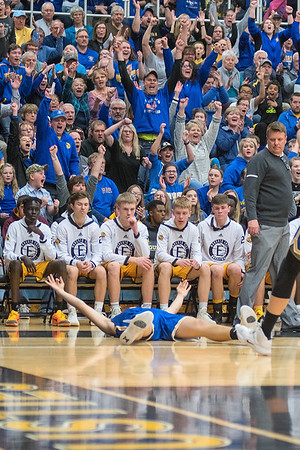 Zach Hoehn of Waseca stays on the ground in front of the Mankato East bench after making a three-pointer and being fouled in the first half of Thursday's game. Photo by Jackson Forderer