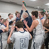 The St. Peter boys basketball team celebrates with head coach Sean Keating after defeating Jordan 71-68 to gain a berth in the Class AA State Boys Basketball Tournament. Photo by Jackson Forderer