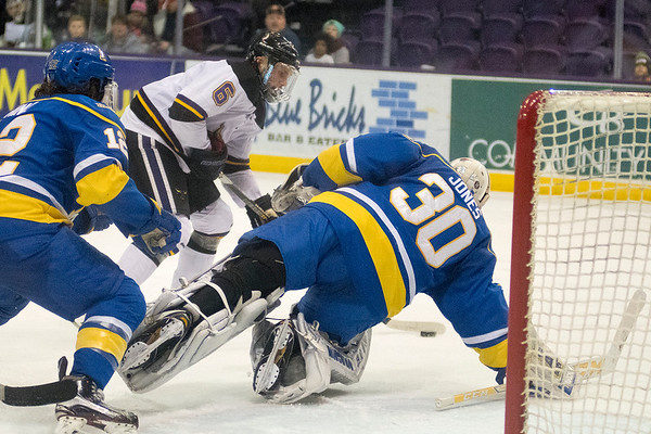 Parker Tuomie (6) of Minnesota State gets goalie Davis Jones (30) to dive for the puck in the second period. Tuomie's two goals lifted MSU to a 3-0 win and a 1-0 series lead. Photo by Jackson Forderer