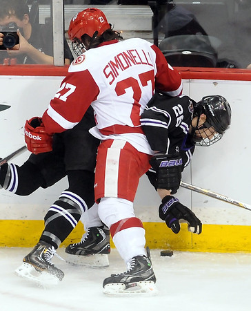 Minnesota State's Dylan Margonari (26) is checked into the boards by Wisconsin's Frankie Simonelli during the first period of their WCHA Final Five game Thursday at the Xcel Energy Center in St. Paul.
